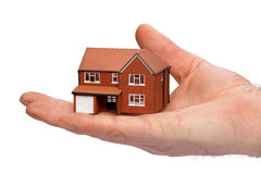 Hand holding a miniature house. Hand holding a miniature modern detached house isolated on a white background stock image