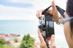 Hand holding a mirrorless digital camera prepare for take a landscape photo Royalty Free Stock Photo