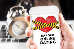 Hand holding mobile with caution tape on heart and Danger online Royalty Free Stock Image