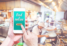 Hand holding mobile with Order food online with blur restaurant. Background, food online business concept.Leave space for adding your text Stock Images
