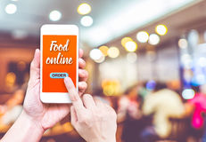 Hand holding mobile with Order food online with blur restaurant. Background, food online business concept.Leave space for adding your text Royalty Free Stock Image
