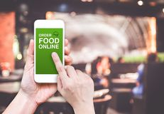 Hand holding mobile with Order food online with blur restaurant. Background, food online business concept.Leave space for adding your text Royalty Free Stock Images