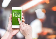 Hand holding mobile with Order food online with blur restaurant. Background, food online business concept.Leave space for adding your text Royalty Free Stock Photos