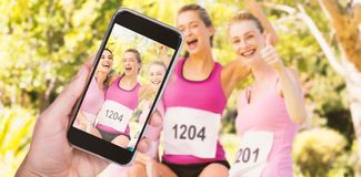 Composite image of hand holding mobile phone against white background. Hand holding mobile phone against white background against young athlete women cheering Stock Photography