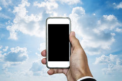 Hand holding mobile phone with blank space on screen, on blue sky with white clouds and bright light behind Stock Images