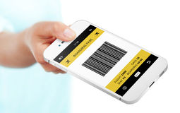 Hand holding mobile phone with boarding pass isolated over white Royalty Free Stock Image
