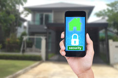 Hand holding mobile phone with concept technology home security Royalty Free Stock Images