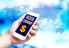 Hand holding mobile phone with Digital economy word with blue bl stock photos