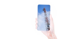 Hand holding mobile phone double exposure with telecom tower Royalty Free Stock Images