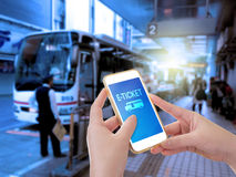 Hand holding mobile phone with E-Ticket word. With blur bus terminal  background,Digital Marketing concept; retro color effected Royalty Free Stock Images