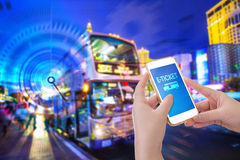 Hand holding mobile phone with E-Ticket word. With blur bus terminal  background,Digital Marketing concept; retro color effected Royalty Free Stock Photography