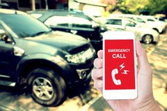 Hand holding mobile phone with Emergency call on screen. With blur car background Stock Photos