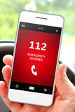 Hand holding mobile phone 112 emergency number. In car stock image