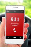 Hand holding mobile phone 911 emergency number in car. Focus on phone royalty free stock image