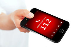 Hand holding mobile phone with emergency number 112. Focus on screen Stock Photos