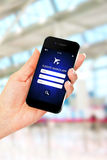 Hand holding mobile phone with flights search application Stock Images