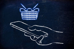 Hand holding mobile phone with glowing shopping cart Royalty Free Stock Photos