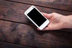 Hand holding mobile phone. Against wooden background Stock Image