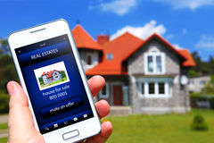 Hand holding mobile phone with house sale offer. And house as a background Stock Image