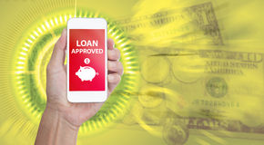 Hand holding mobile phone with Loan approved word. On blur business graphic  background Stock Photos