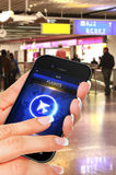 Hand holding mobile phone and looking for flights on airport Royalty Free Stock Photography
