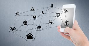 Hand holding mobile phone and networking icons on grey background Stock Photo