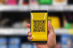 Hand holding mobile phone scanning QR code on blurred goods shel. F in supermarket, business technology concept Royalty Free Stock Photography