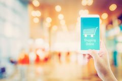 Hand holding mobile phone with shopping online on screen. With blur supermarket background, shop online concept stock photos