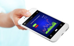 Hand holding mobile phone with stock exchange chart over white Royalty Free Stock Images