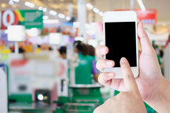 Hand holding mobile phone at supermarket checkout background. Digital wallet concept royalty free stock photos
