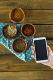 Hand holding mobilephone and various spices in bowl. Hand holding mobile phone and various spices in bowl on wooden table Stock Photos