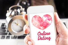 Hand holding mobile with red heart and online dating word on screen with clock and laptop at background, Internet love concept.  royalty free stock images