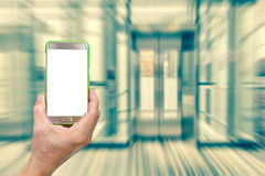 Hand holding mobile smart phone with abstract blur elevator back Royalty Free Stock Photos