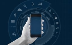 Hand holding mobile smart phone, and application icons background. S stock image