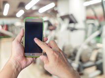 Hand holding mobile smart phone with blur fitness gym equipment Royalty Free Stock Photo