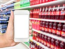Hand holding mobile smart phone on drink bottles display. On shelves in a supermarket blur background Stock Image