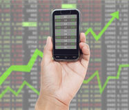 Mobile smart phone and exchange report. Hand holding mobile smart phone and exchange report Stock Photo