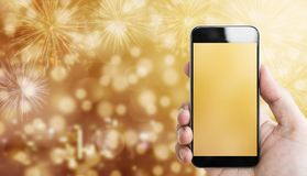 Hand holding mobile smart phone, luxury gold Bokeh light with fireworks background. S Stock Photography