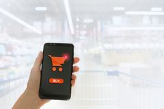 Hand holding mobile smart phone with my shopping carts screen on Supermarket blur background.  royalty free stock photos