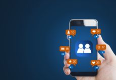 Hand holding mobile smart phone, with notification icons and online community icon on screen. Hand holding mobile smart phone, with notification icon and online stock image
