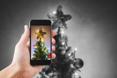 Hand holding mobile smart phone, taking photo of Christmas star on Christmas tree with colorful lights Royalty Free Stock Image