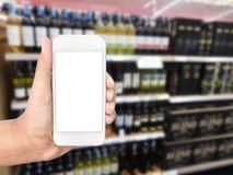 Hand holding mobile smart phone on wine Liquor bottle. On shelf, Blurred background Stock Photo