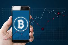 Hand holding mobile smartphone with B symbol of Bitcoin, internet banking and block chain on screen and raising graph background stock photos
