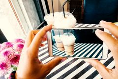 Hand holding mobile and taking photo of iced coffee stock photo