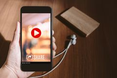 Hand holding mobile watching viral video advertising on phone sc. Reen at blur wood table,share video on social media concept,Digital marketing strategy Royalty Free Stock Photos