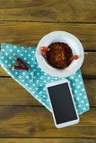 Hand holding mobilephone and chilli flakes in bowl. On wooden table Royalty Free Stock Photo