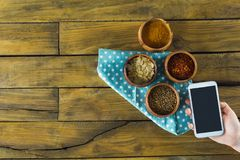 Hand holding mobilephone and various spices in bowl. On wooden table Stock Image
