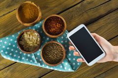 Hand holding mobilephone and various spices in bowlq. Hand holding mobilephone and various spices in bowl on wooden table Royalty Free Stock Photos