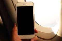 Hand holding mockup smartphone with plane window background Royalty Free Stock Images