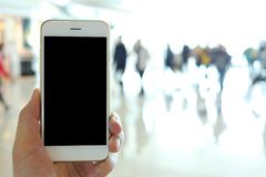 Hand holding mockup smartphone with airport passenger terminal b Stock Photos